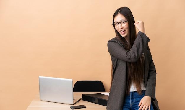 Chinesische geschäftsfrau an ihrem arbeitsplatz macht starke geste