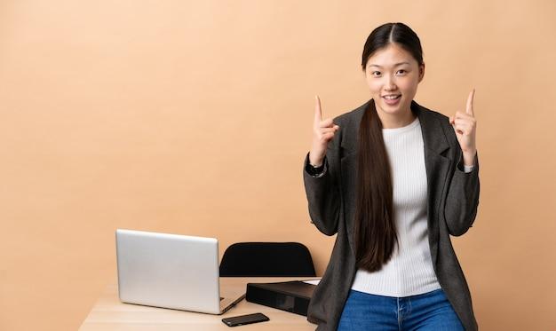 Chinesische geschäftsfrau an ihrem arbeitsplatz zeigt eine großartige idee auf