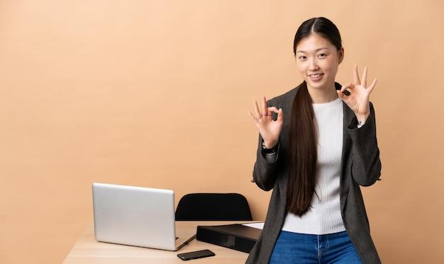 Chinesische geschäftsfrau an ihrem arbeitsplatz zeigt ok zeichen mit zwei händen