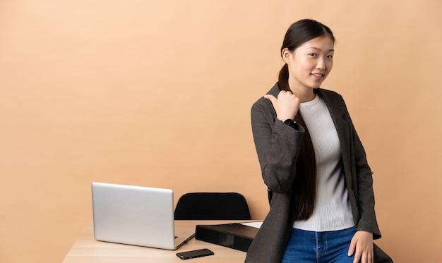 Chinesische geschäftsfrau an ihrem arbeitsplatz zeigt zur seite, um ein produkt zu präsentieren
