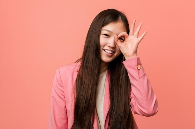 Chinesische geschäftsfrau, die rosa anzug trägt, aufgeregt aufgeregt, ok geste auf auge haltend.