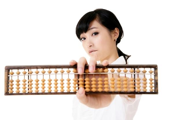 Chinesische geschäftsfrau, die traditionellen abakus auf weißem hintergrund hält.
