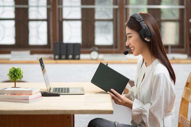 Chinesische geschäftsfrau mit kopfhörervideoanruf unter verwendung des laptops für kundendienst