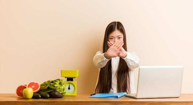 Chinesische junge ernährungswissenschaftlerin, die mit ihrem laptop arbeitet, der eine verweigerungsgeste tut