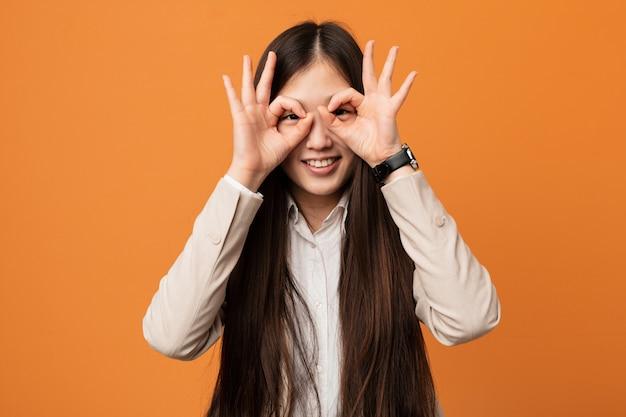 Chinesische junge geschäftsfrau, die okay zeichen über augen zeigt