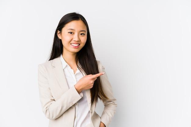 Chinesische junge geschäftsfrau lokalisierte lächelnd und zeigte zur seite und zeigte etwas an der leeren stelle.