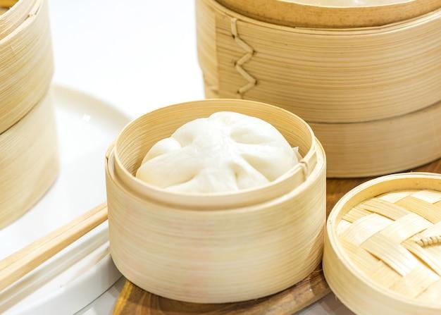 Chinesische knödel gedämpfte brötchen, gedämpftes brötchen in holzkorb serviert