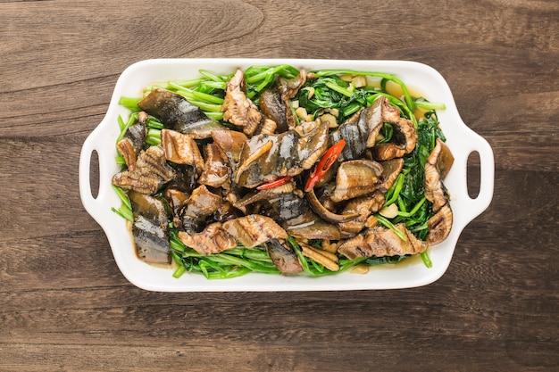 Chinesische küche: gebratener aal mit einem teller kohl