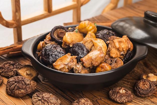 Chinesische küche: gebratenes hähnchen mit kastanien und pilzen