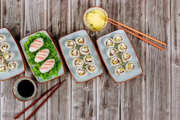 Chinesische küche set sushi-rollen mit sojasauce, ingwer und essstäbchen.