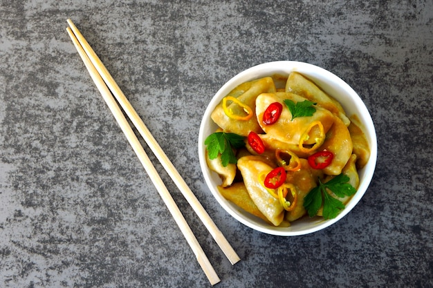 Chinesische mehlklöße in der weißen schüssel mit paprikapfeffer