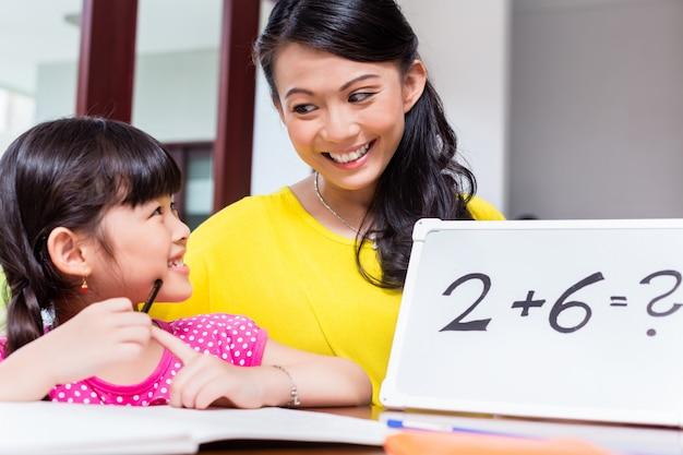 Chinesische mutter, die dem kind mathematik beibringt