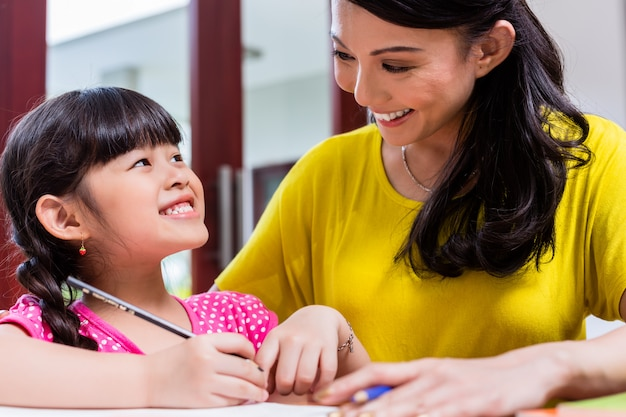 Chinesische mutter, die ihr kind zu hause unterrichtet