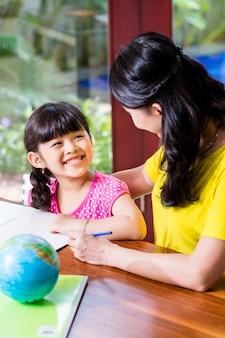 Chinesische mutter, die schulhausarbeit mit kind tut