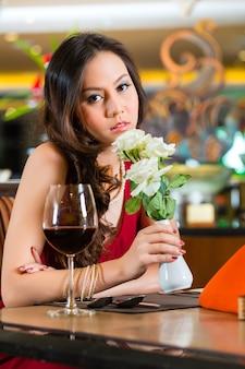 Chinesische nervöse, hoffnungsvolle, einsame, verträumte, herzkranke frau in einem restaurant, die auf ein date wartete, stand auf