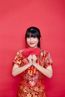 Chinesische neujahrsjunge frau, die roten cheongsam hält umschlag hält