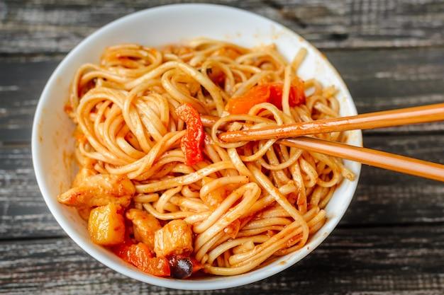 Chinesische nudel in der sauer-süßen soße und in den essstäbchen auf tabelle