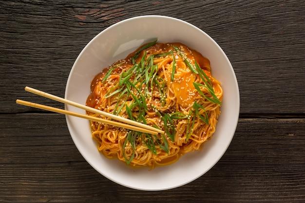 Chinesische nudel. mit stäbchen und chinesischen nudeln in süß-saurer sauce in einer schüssel