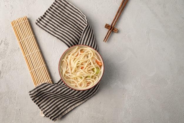 Chinesische nudel oder udon mit gemüse und essstäbchen auf lokalisiertem weiß
