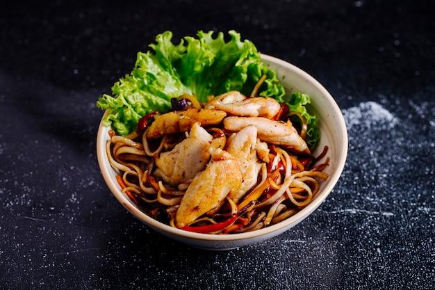 Chinesische nudeln in schüssel mit filet und salat.