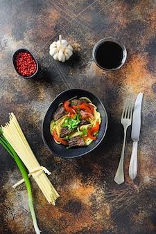 Chinesische nudeln mit gemüse und rindfleisch in der draufsicht der schwarzen schüssel.