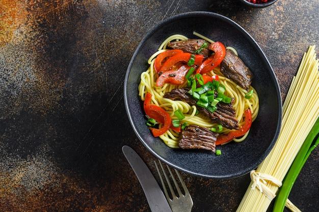 Chinesische nudeln mit gemüse und rindfleisch in schwarzer schüssel