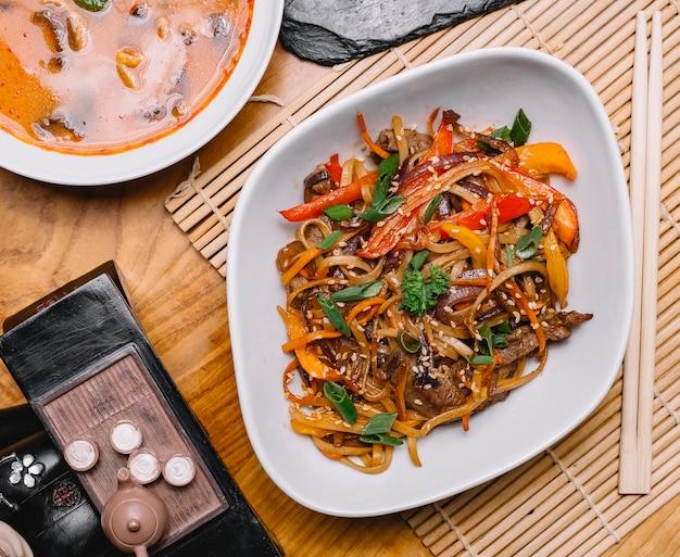 Chinesische nudeln von oben mit gemüse und fleisch