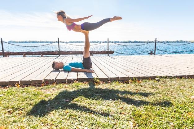Chinesische paare, die akrobatisches yoga am park in toronto üben