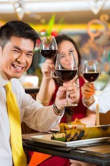 Chinesische paare, die mit wein im restaurant rösten