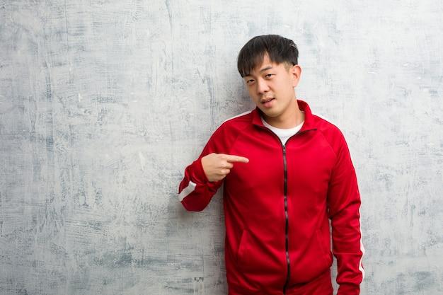 Chinesische person der jungen sportfitness, die von hand auf eine leere stelle des hemdes zeigt, stolz und zuversichtlich