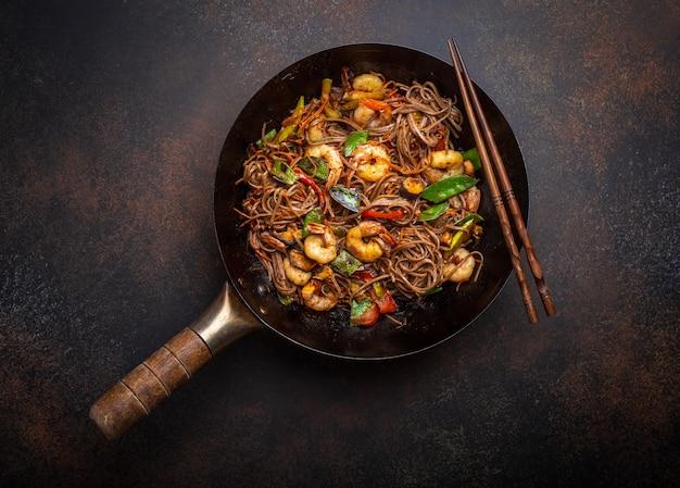 Chinesische soba-stir-fry-nudeln mit garnelen, gemüse in alter rustikaler wok-pfanne serviert auf betonhintergrund, nahaufnahme, draufsicht. traditionelles asiatisches/thailändisches gericht, nahaufnahme
