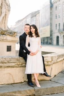 Chinesische süße braut und bräutigam junge jungvermählten gerade verheiratetes paar, das auf der steintreppe auf straßen der alten stadt am hochzeitstag aufwirft.