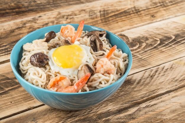 Chinesische suppe mit udonnudeln, schweinefleisch, gekochten eiern, pilzen und garnelennahaufnahme in einer schüssel auf dem tisch