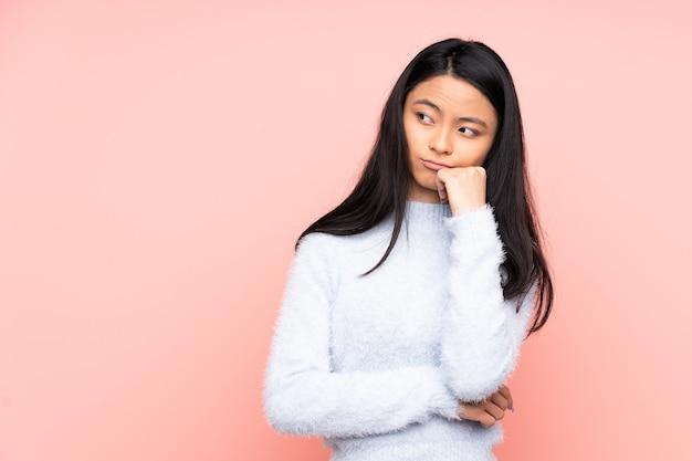 Chinesische teenager-frau lokalisiert auf rosa mit müde und gelangweiltem ausdruck
