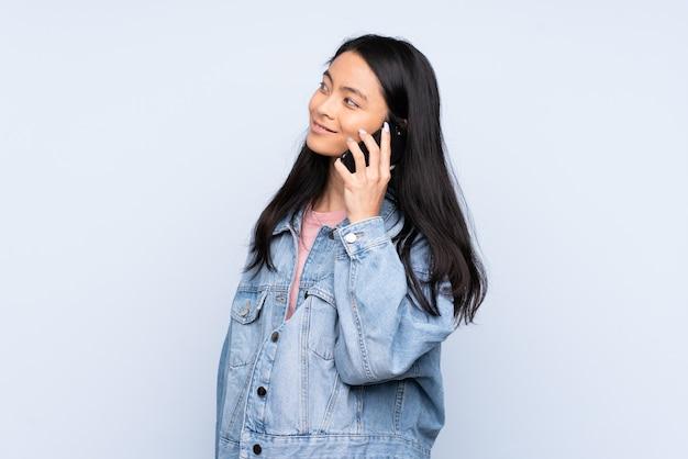 Chinesische teenagerfrau isoliert auf blau, die ein gespräch mit dem handy mit jemandem hält