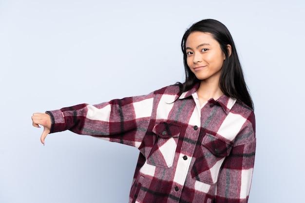Chinesische teenagerfrau lokalisiert auf blau, das daumen unten mit negativem ausdruck zeigt