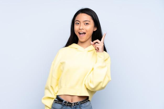 Chinesische teenagerfrau lokalisiert auf blau denkend eine idee, die den finger nach oben zeigt