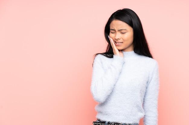Chinesische teenagerfrau lokalisiert auf rosa mit zahnschmerzen