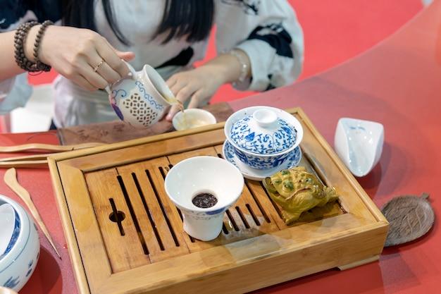 Chinesische teezeremonie. das mädchen gießt den tee aus dem wasserkocher in die tasse.