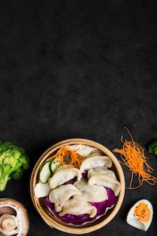 Chinesische teigtaschen auf dem traditionellen dampfer mit salat und gekochten eiern