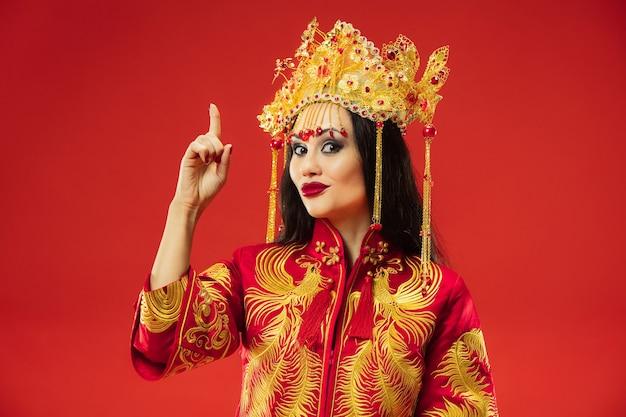 Chinesische traditionelle anmutige frau im studio über rotem hintergrund. schönes mädchen, das nationaltracht trägt. chinesisches neujahr, eleganz, anmut, darsteller, performance, tanz, schauspielerin, emotionskonzept
