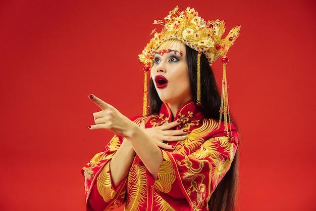 Chinesische traditionelle anmutige frau im studio über rotem hintergrund.