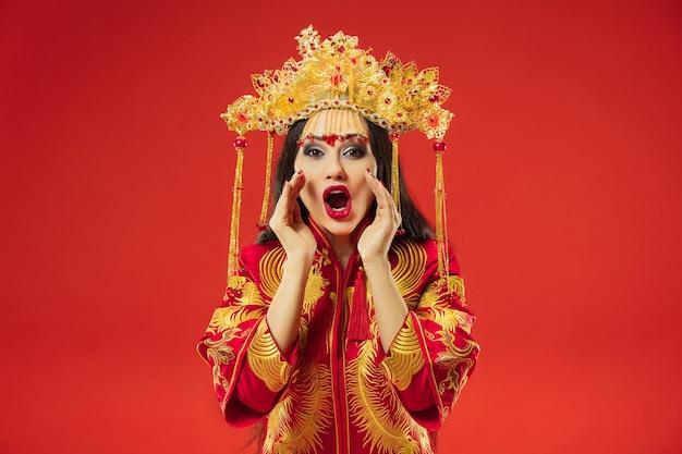 Chinesische traditionelle anmutige frau im studio über roter wand