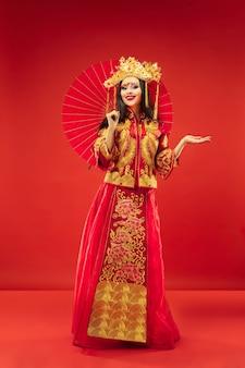 Chinesische traditionelle anmutige frau über rotem hintergrund. schönes mädchen, das nationaltracht trägt. chinesisches neujahr