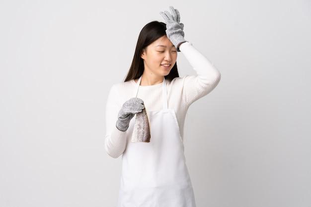 Chinesischer fischhändler, der eine schürze trägt und einen rohen fisch auf isoliertem weiß hält, hat etwas erkannt und beabsichtigt, die lösung zu finden