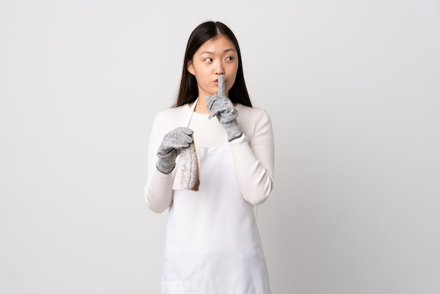 Chinesischer fischhändler, der eine schürze trägt und einen rohen fisch über isolierte weiße wand hält, die ein zeichen der schweigegeste zeigt, die finger in den mund setzt