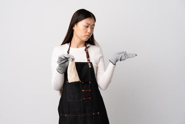 Chinesischer fischhändler, der eine schürze trägt und einen rohen fisch über isolierter weißer wand hält, die copyspace mit zweifeln hält