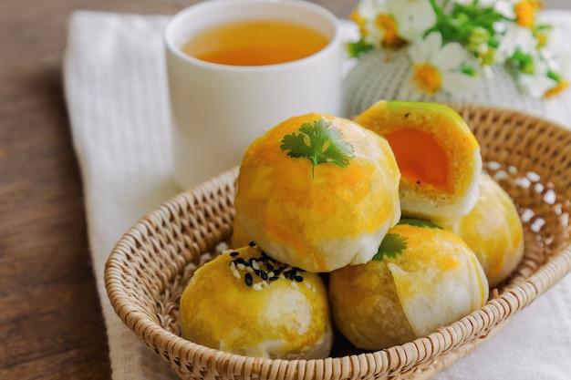 Chinesischer gebäck- oder mondkuchen füllte mit mungobohnenpaste und gesalzenem eigelb, die mit tee gedient wurden