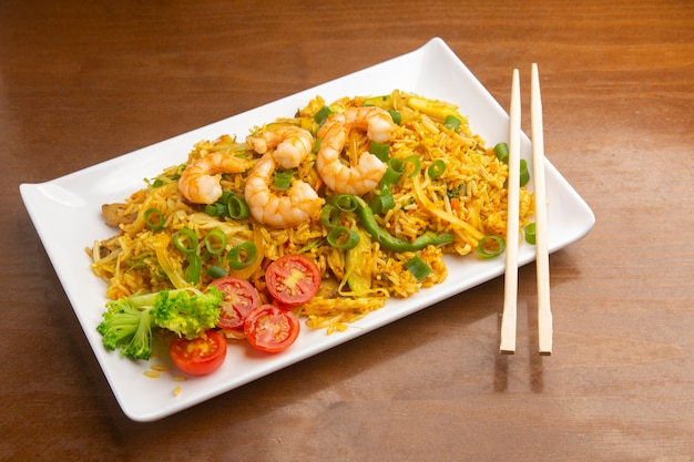Chinesischer gebratener reis mit garnelen, auf holz. typisch asiatisches essen.