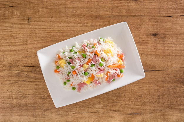 Chinesischer gebratener reis mit gemüse und omelett auf draufsicht des holztischs